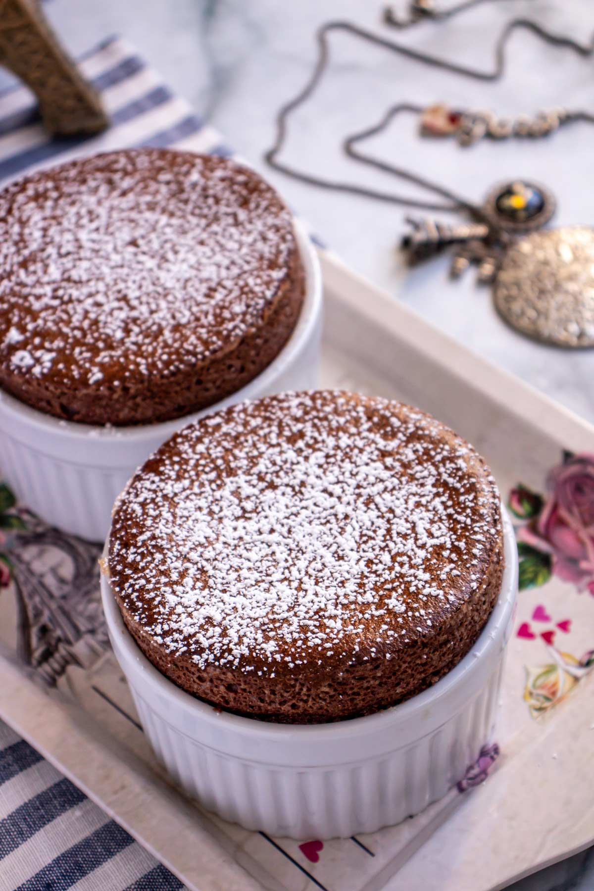 Two chocolate soufflés dusted with powdered sugar on a small decorative tray.