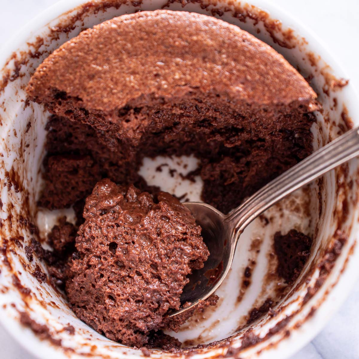 A half-eaten chocolate soufflé with a spoon scooping some up.