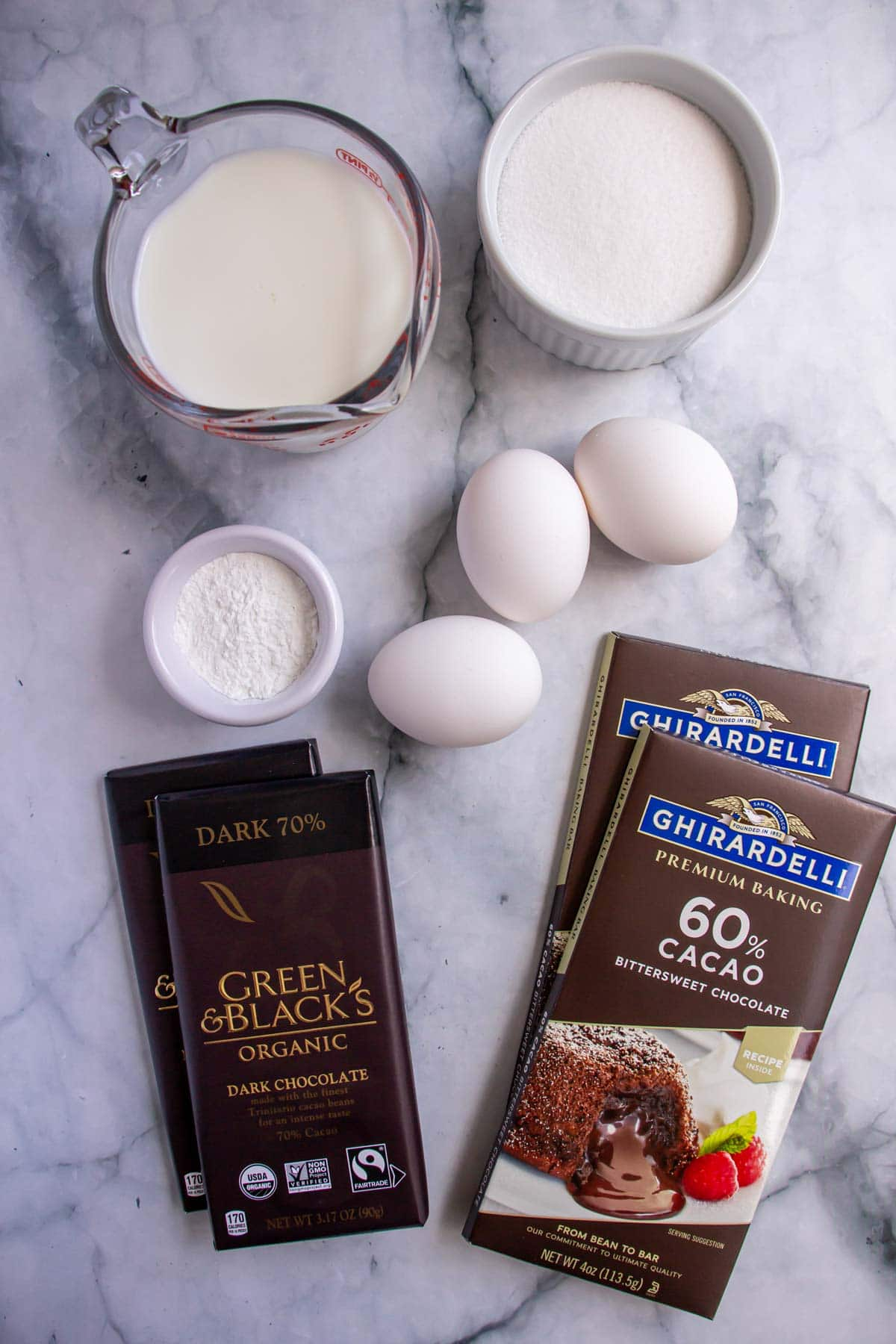 Ingredients for chocolate soufflés on a white marble background.
