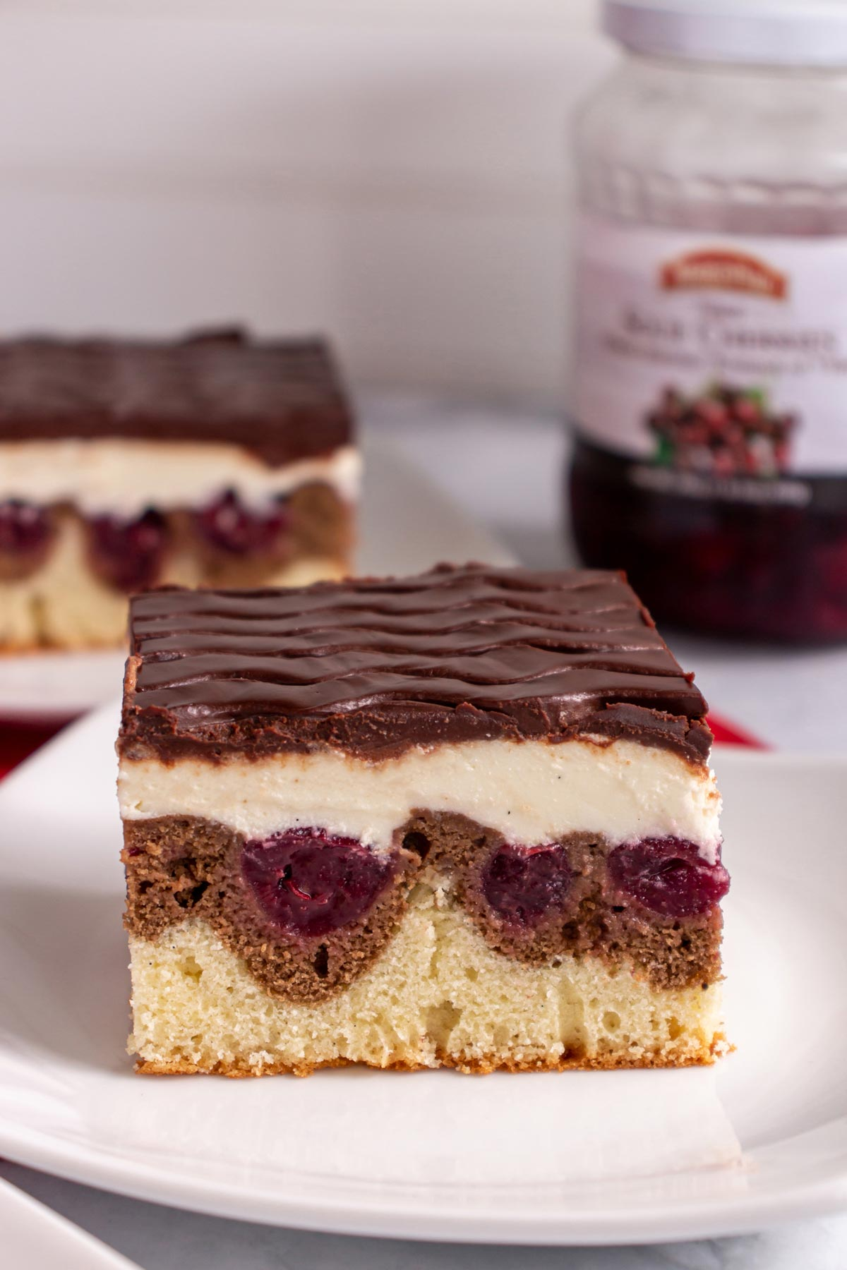 Closeup of a square slice of Danube wave cake with cream and chocolate on top.