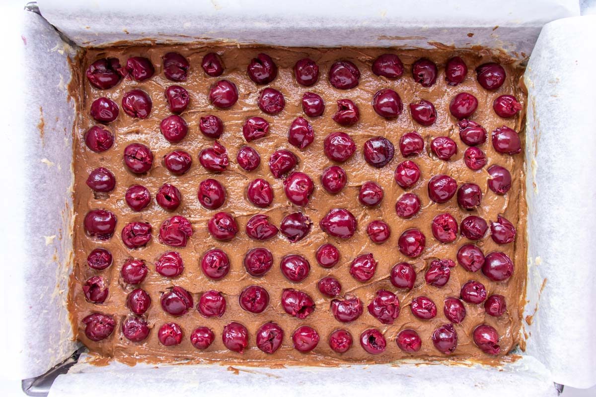 Sour cherries arranged in rows over the top of chocolate cake batter in a rectangular pan.