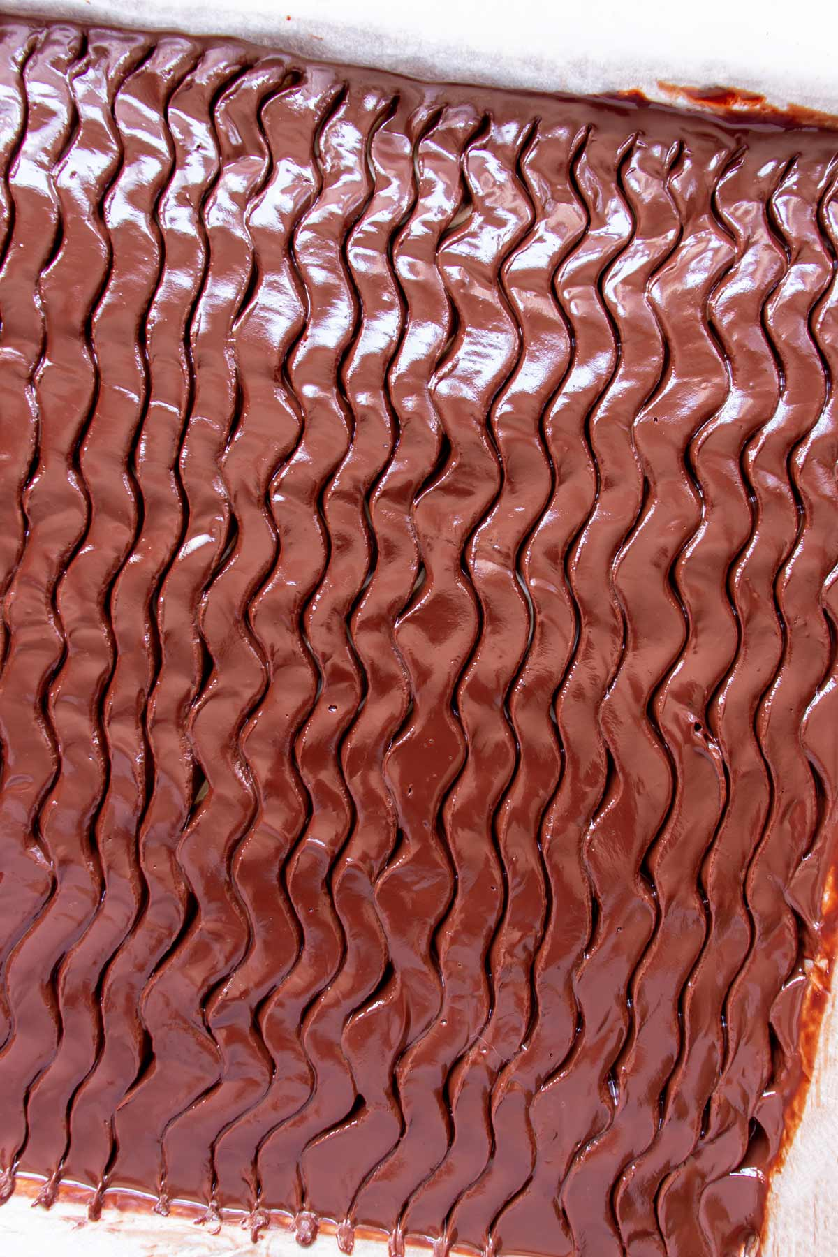 Closeup of a wavy pattern in chocolate ganache on top of a cake.