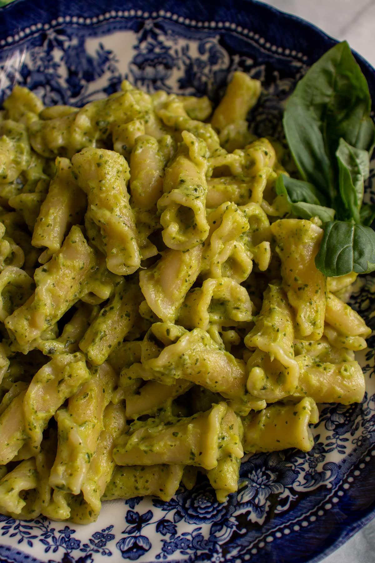 Closeup of a blue bowl filled with campanelle pasta tossed in green pureed zucchini sauce.