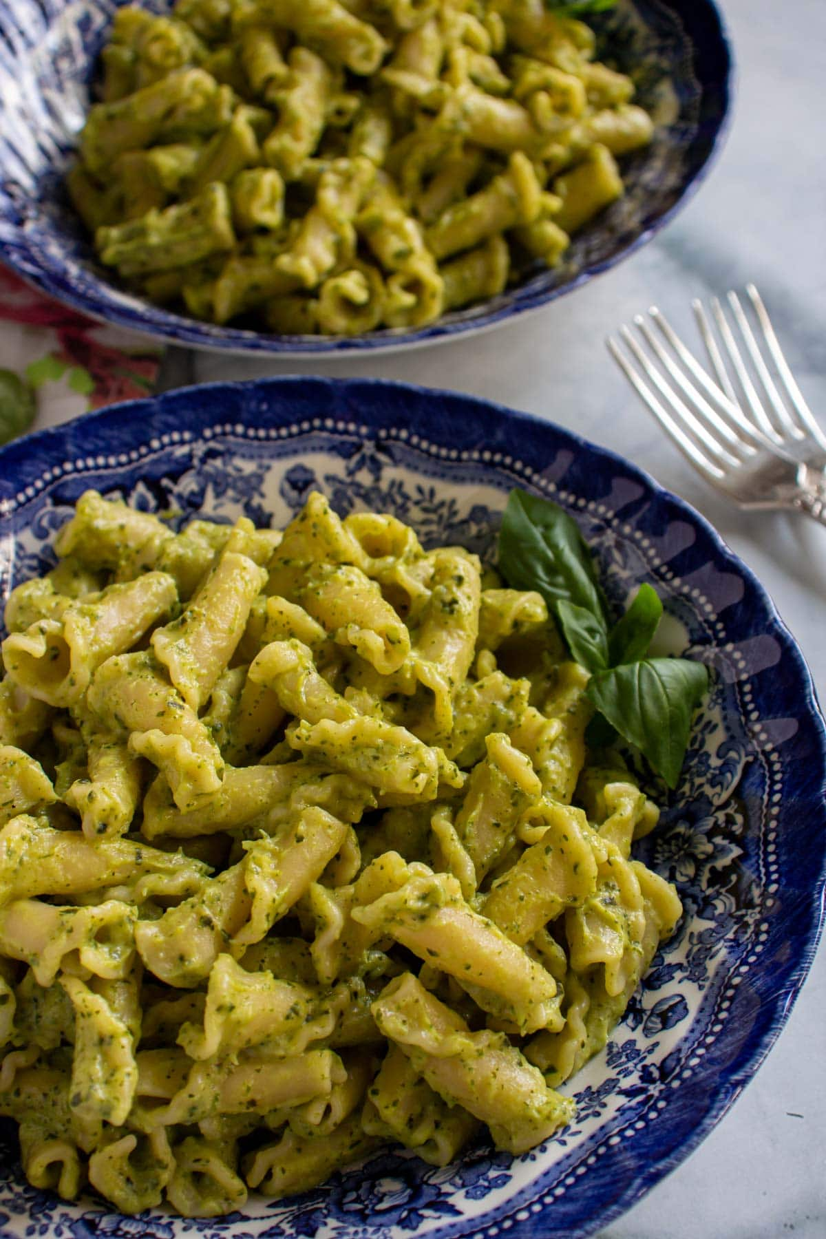 Two bowls of campanelle pasta in green sauce garnished with basil.