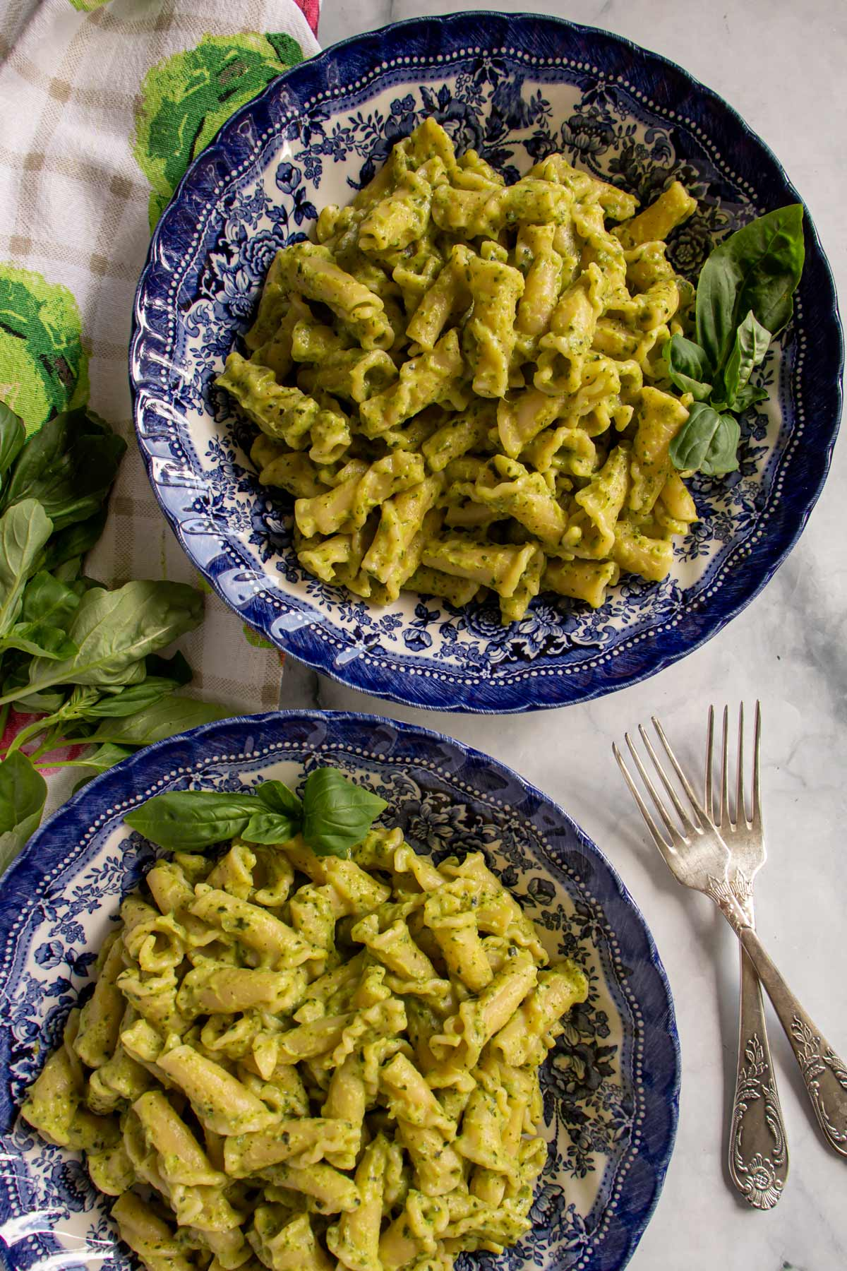 Two blue bowls of campanelle pasta tossed in green pureed zucchini sauce next to two forks.