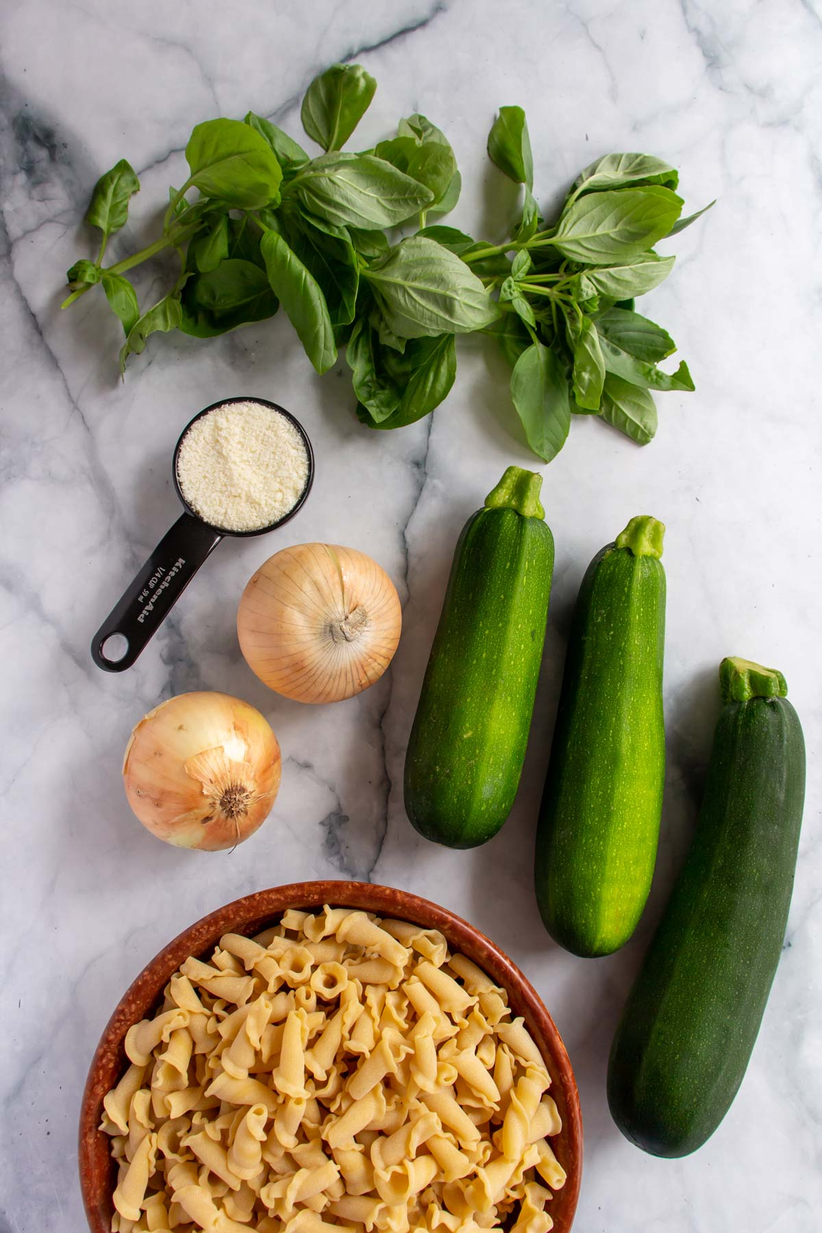 Ingredients for pasta with zucchini sauce on a white marble background.
