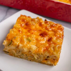 A square piece of macaroni pie on a plate with a red dish in the background.