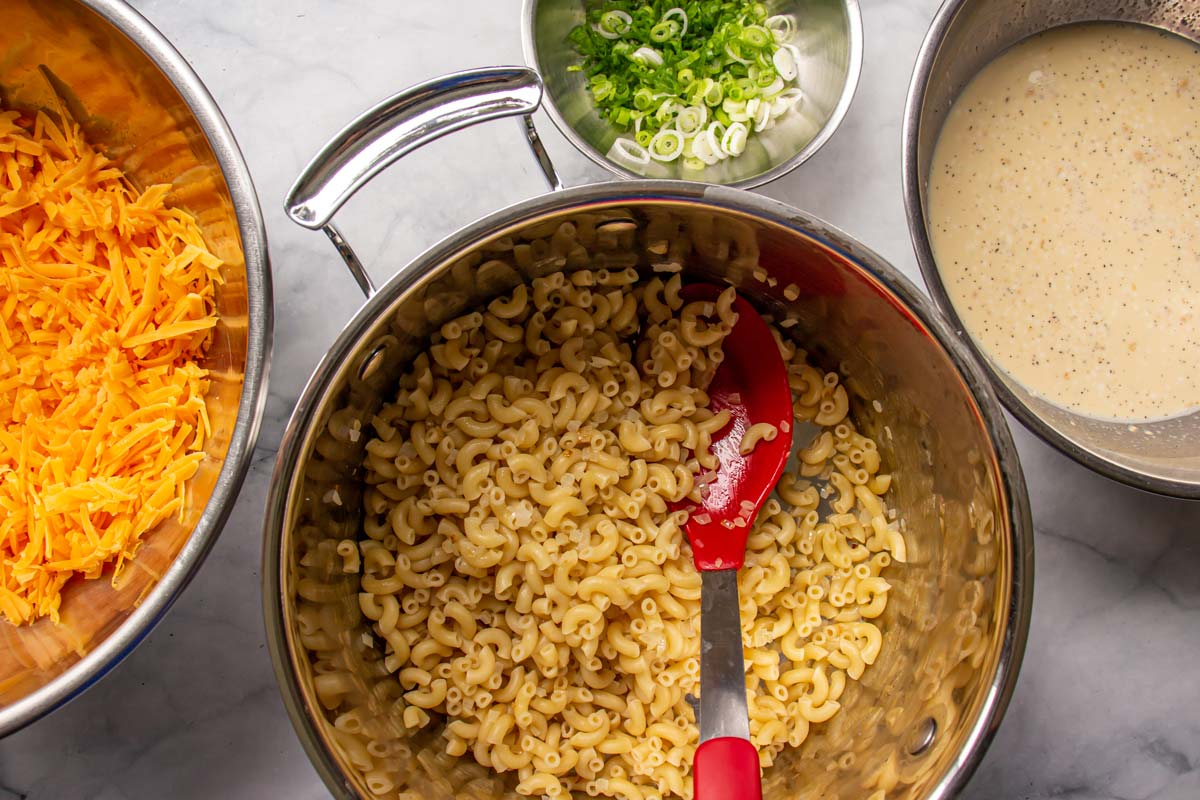 Cooked elbow macaroni in a pot surrounded by bowls of cheese, scallions, and white sauce.