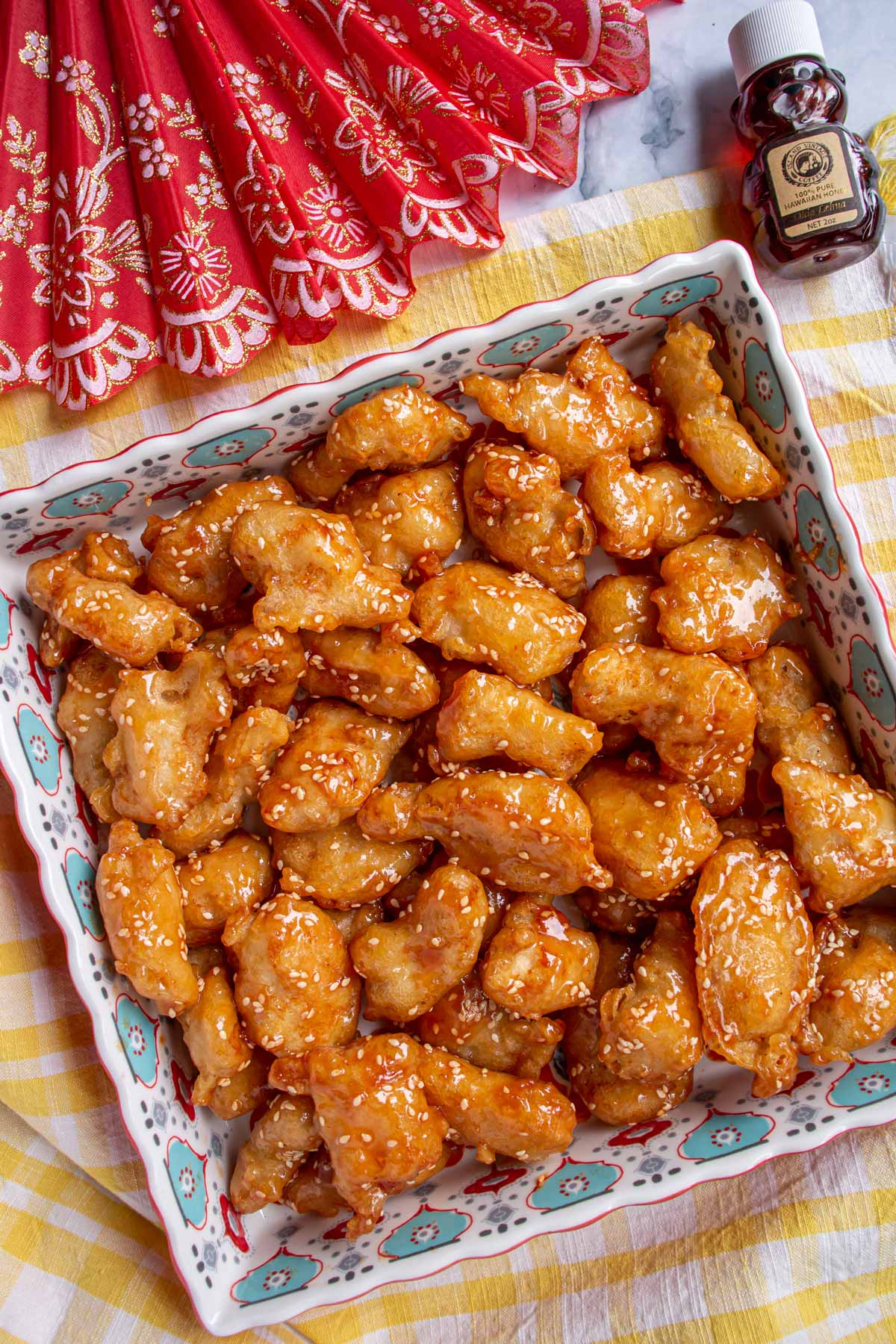 A colorful square dish filled with Chinese honey sesame chicken next to a red folding fan.