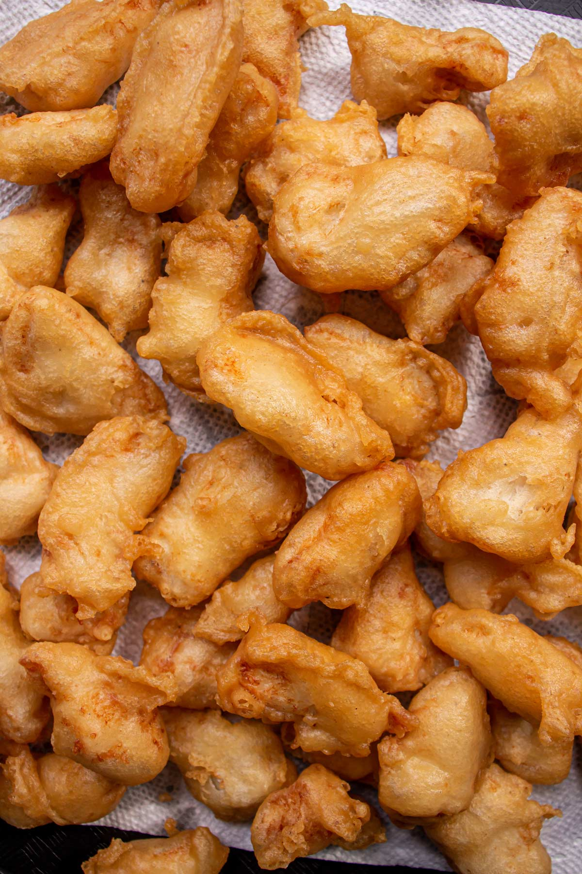 Small rectangular strips of battered fried chicken piled on a surface.