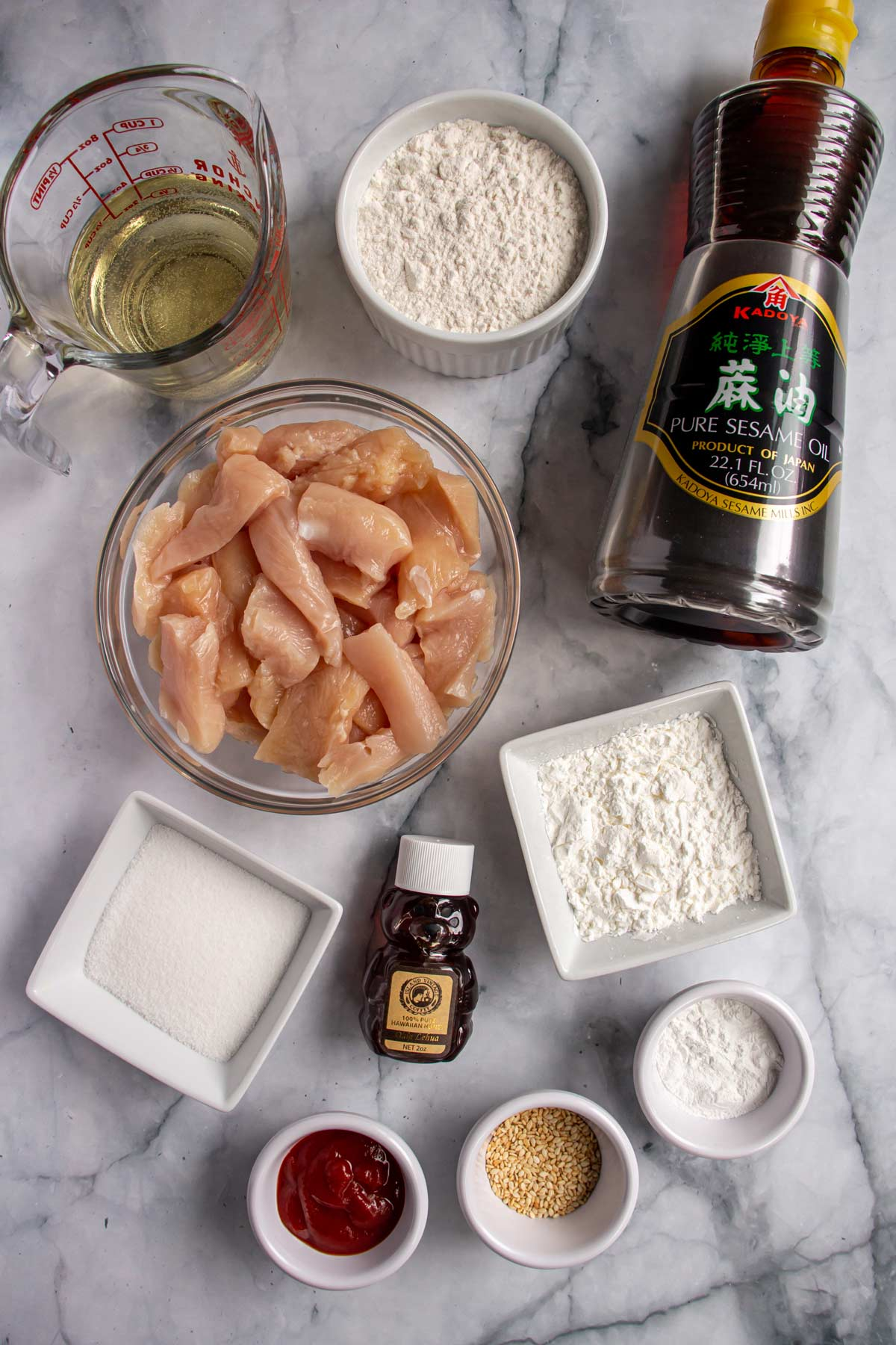 Ingredients for honey sesame chicken on a white marble background.