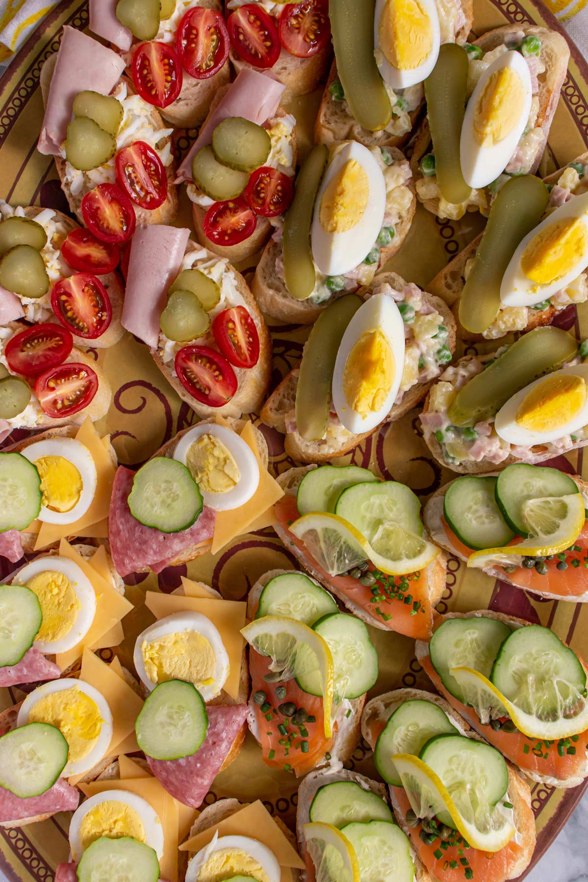 Four varieties of Czech open-faced sandwiches on a large oval platter.