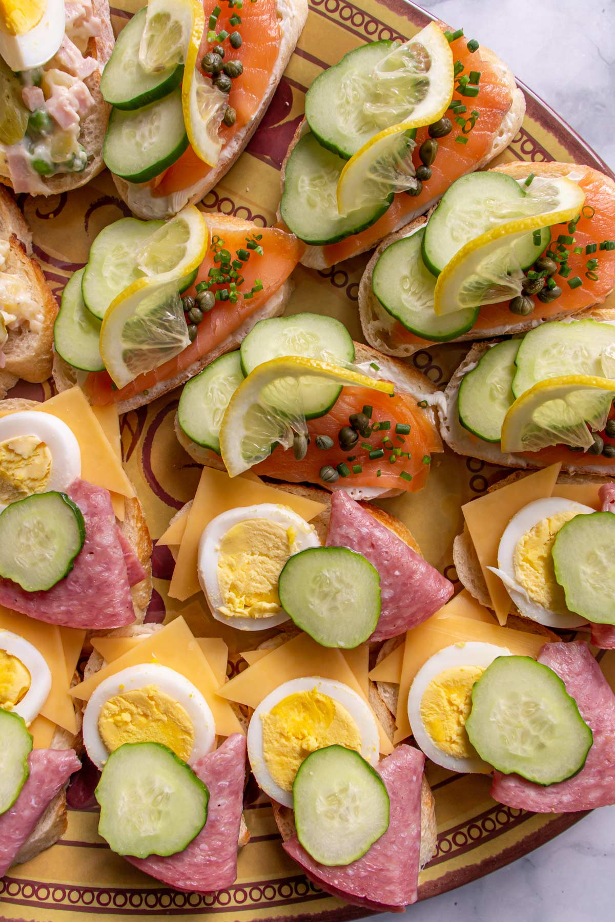 Two varieties of Czech open-faced sandwiches topped with salami and cheese and smoked salmon.