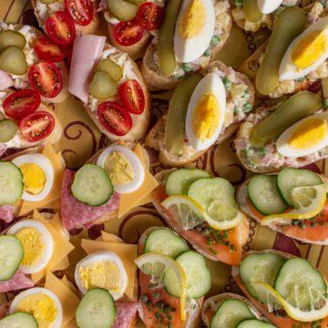 Closeup of four varieties of Czech open-faced sandwiches on a platter.