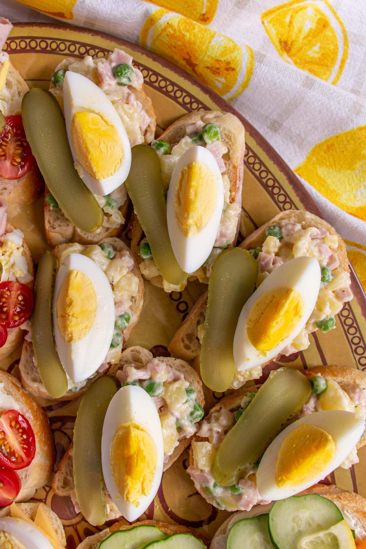 Open-faced sandwiches topped with potato salad, hard-boiled egg and pickle.