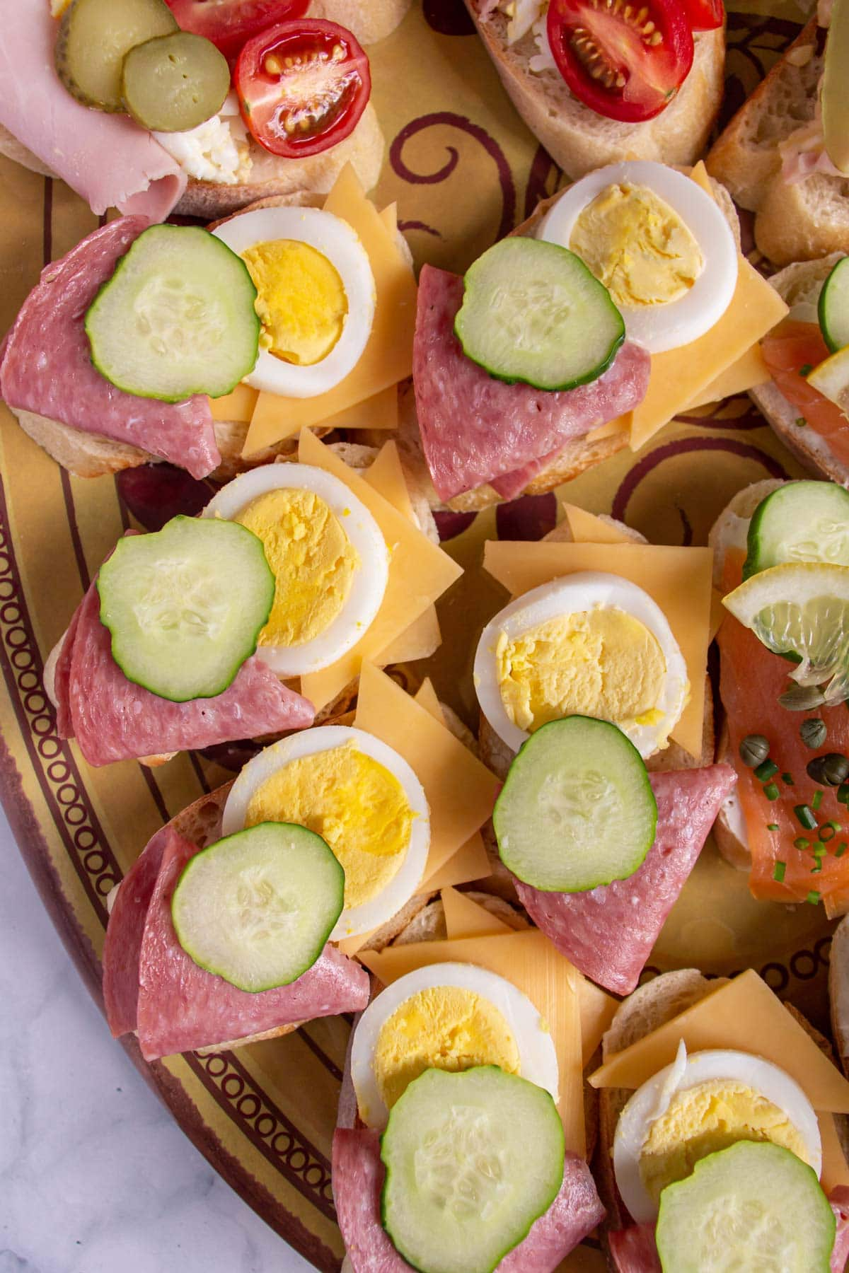 Open-faced sandwiches topped with salami, cheese, hard-boiled egg, and cucumber.