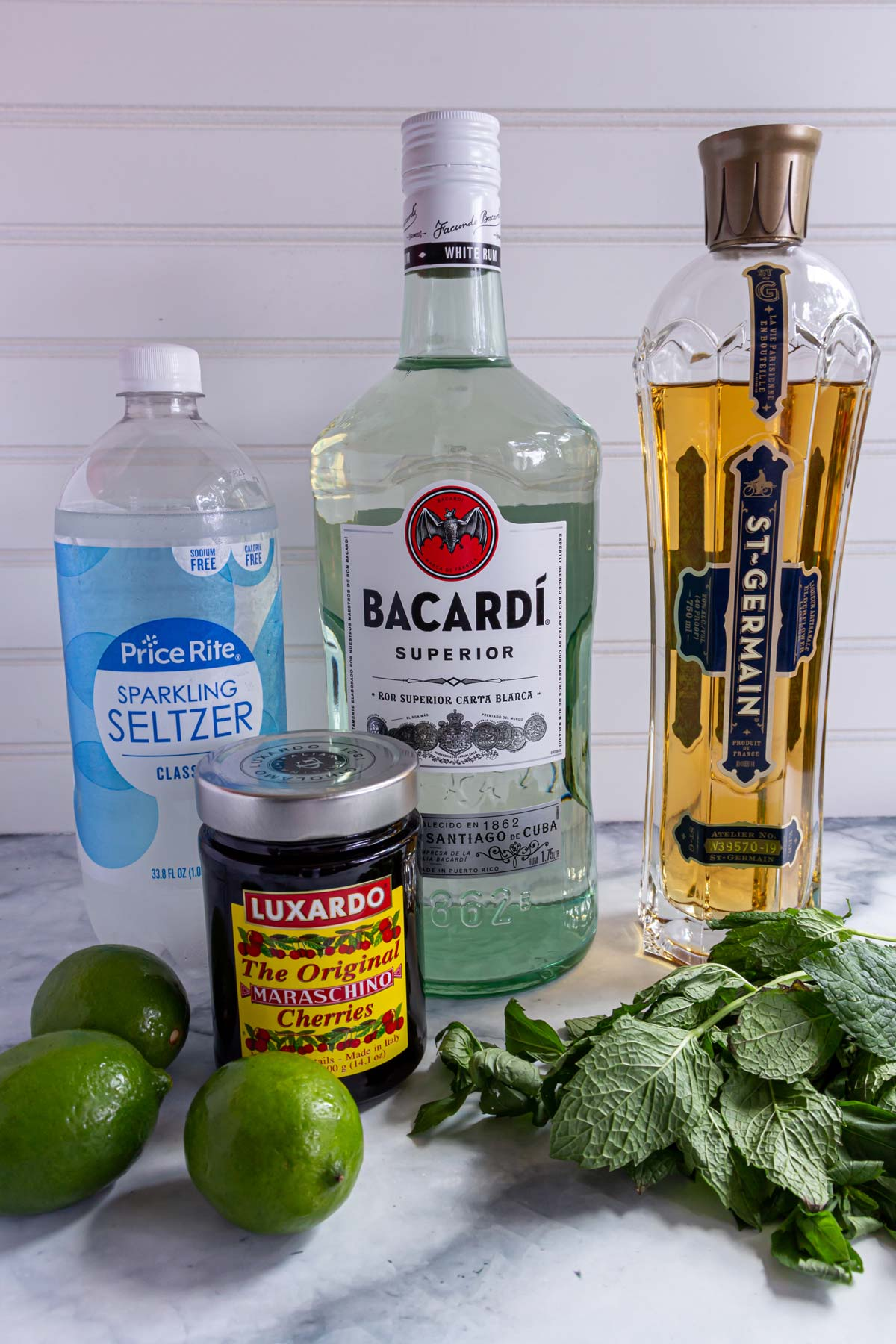 Bottles of seltzer, rum, St. Germain and Luxardo cherries, limes, and fresh mint.