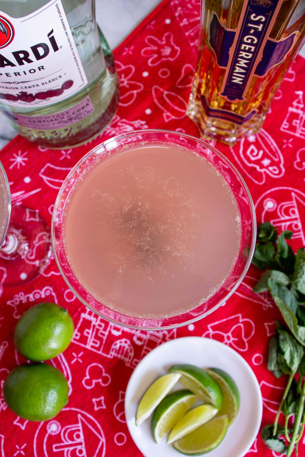 A blush colored drink in a cocktail glass surrounded by limes, mint and alcohol bottles.