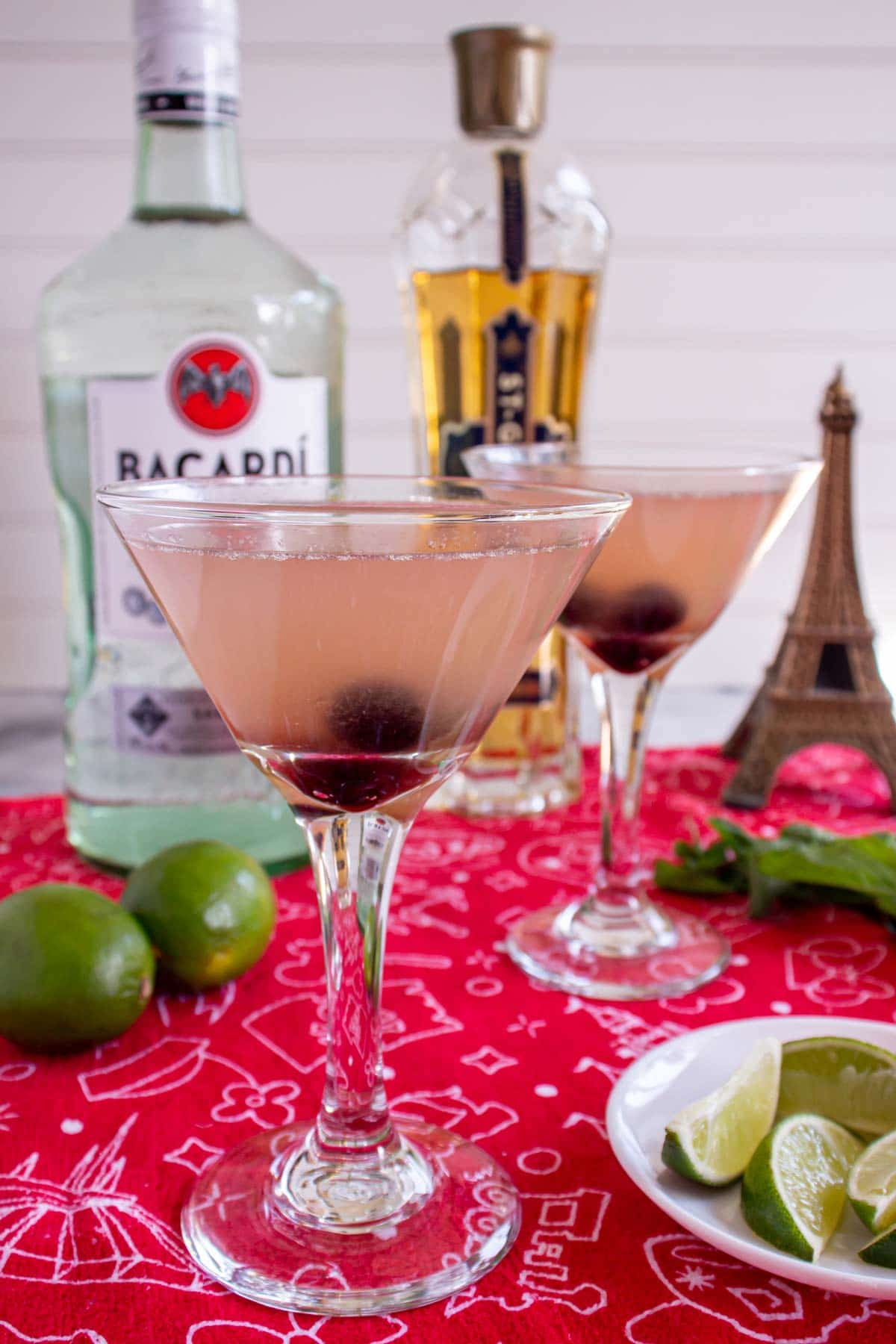 Two martini glasses with drinks garnished with black cherries on a red surface.