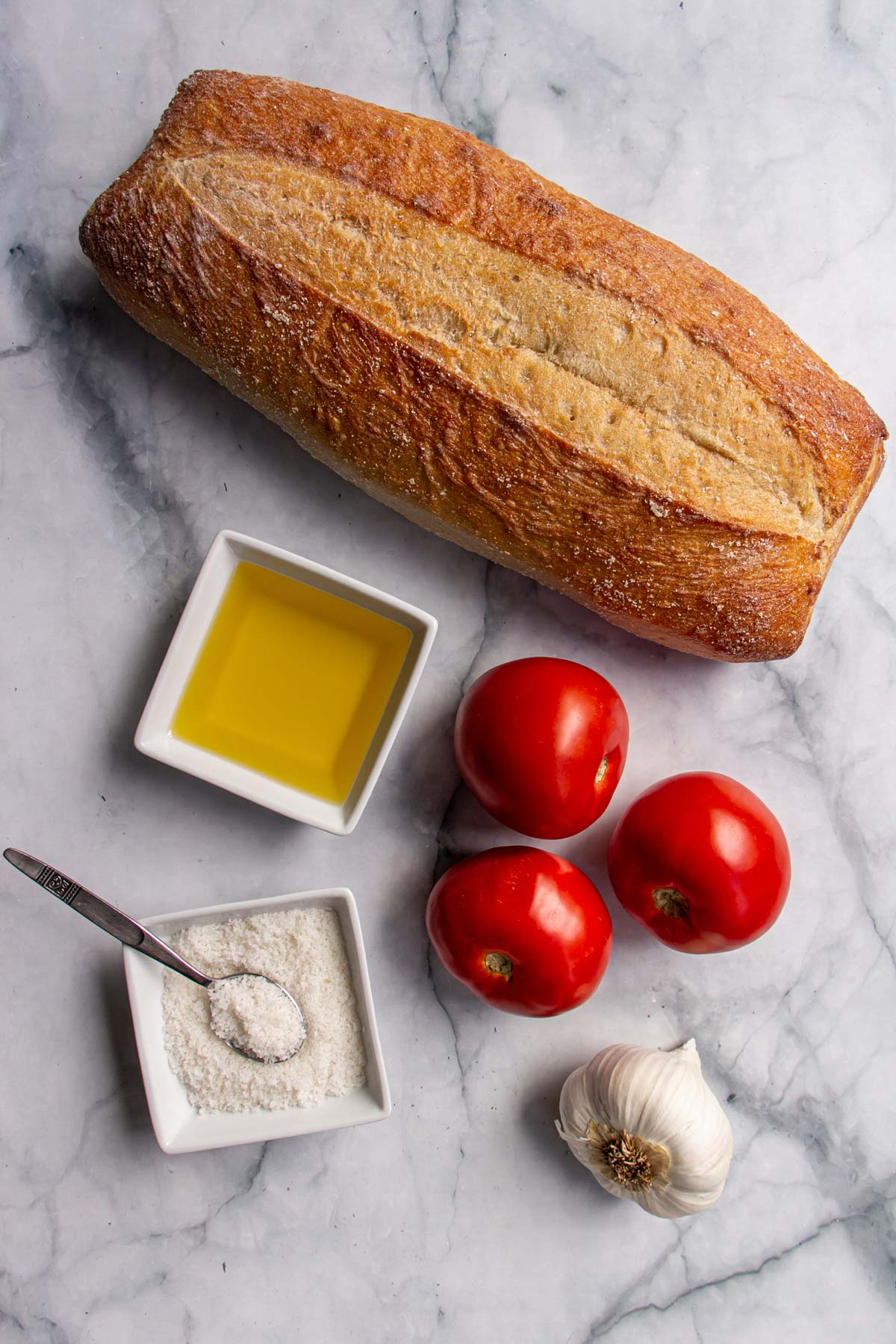 Ingredients for pan con tomate on a white marble surface.