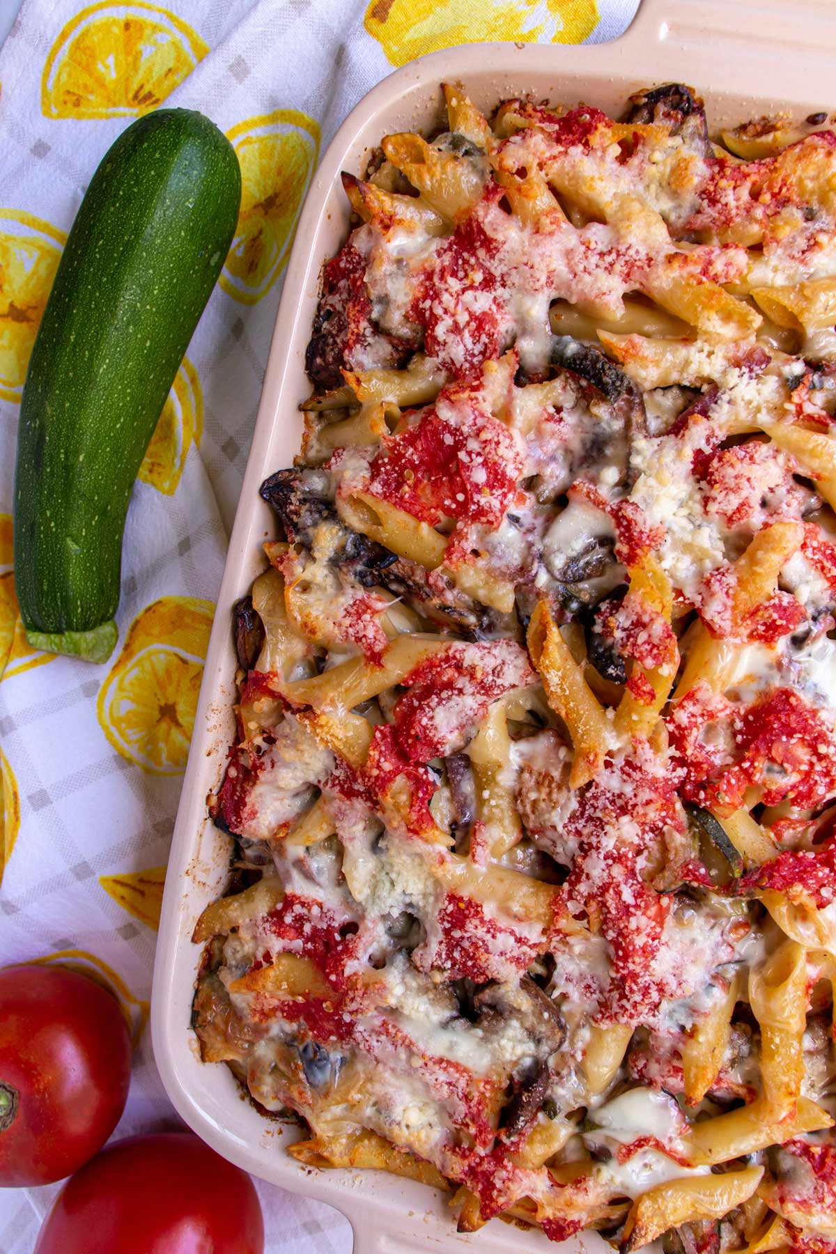 Baked pasta in a rectangular baking dish with a zucchini and tomatoes on the side.