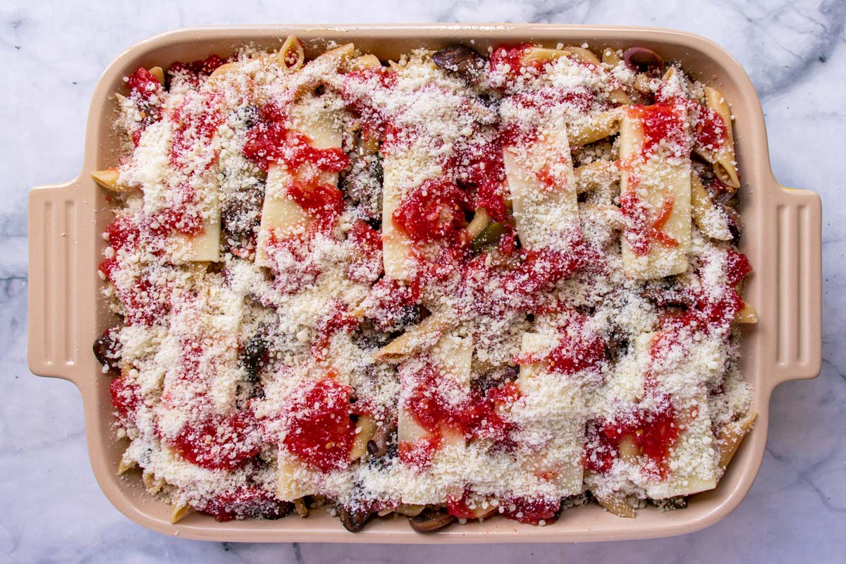 An assembled but unbaked pasta casserole with cheese on top.