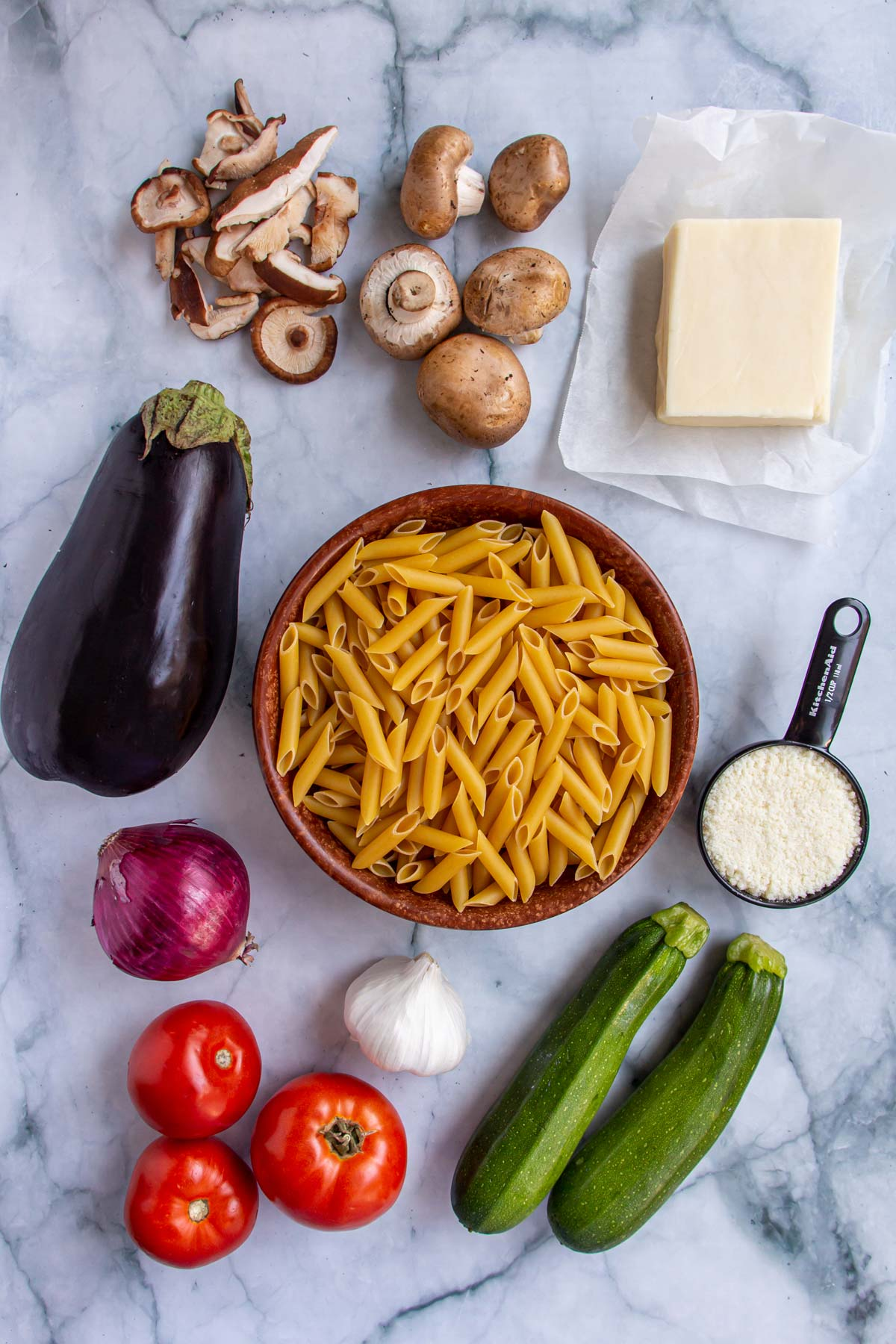 Ingredients for pasta al forno with roasted vegetables on a white marble background.