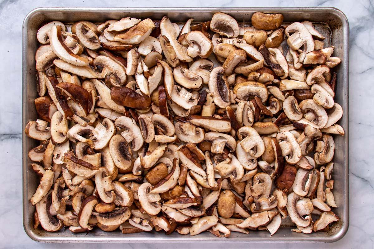 Sliced mushrooms on a rectangular baking sheet.