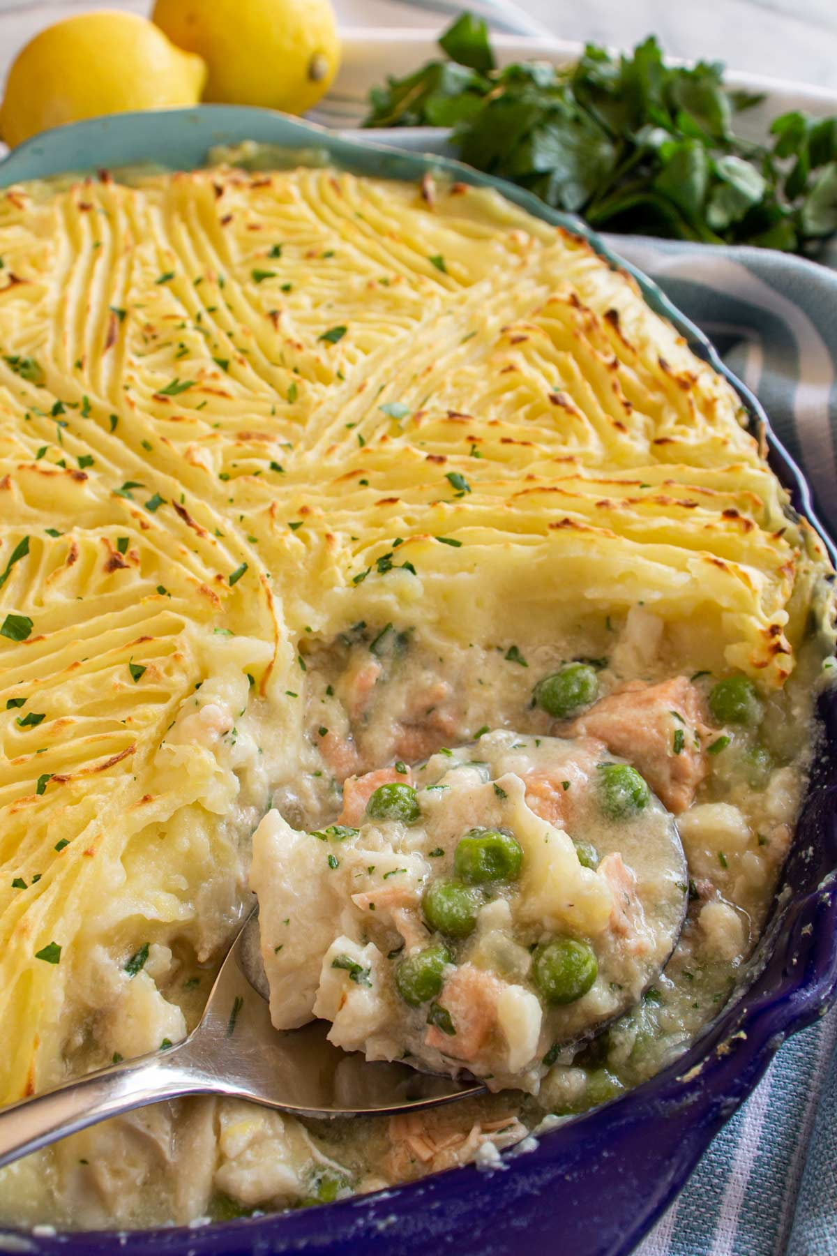 Fish pie with peas in an oval baking dish with a spoon scooping some out.