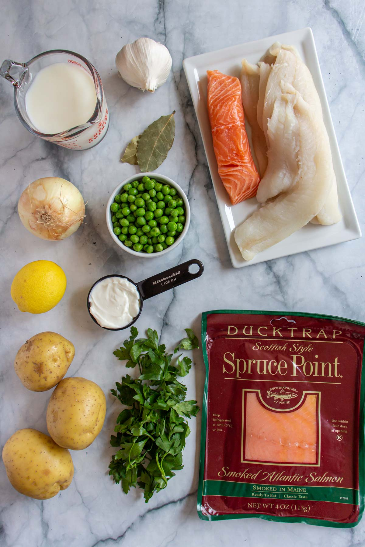 Ingredients for British fish pie on a white marble background.