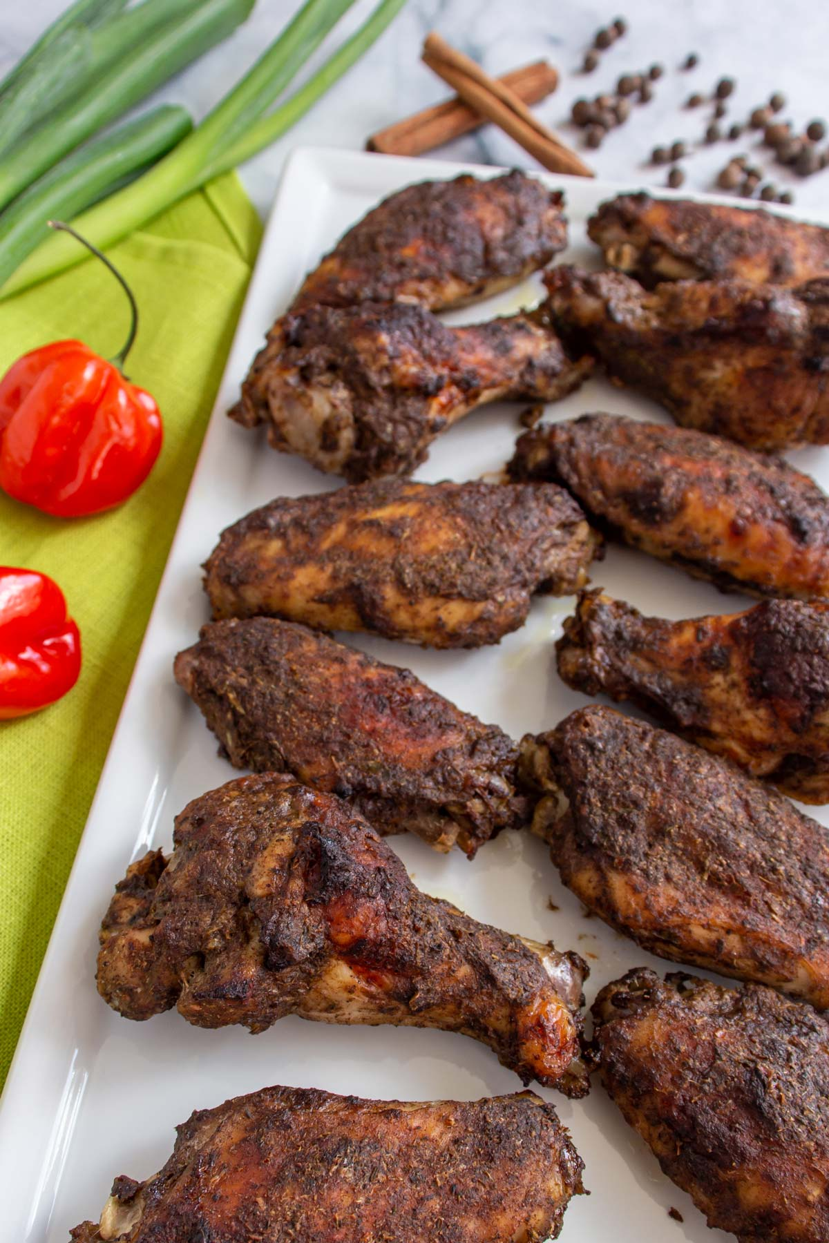 Baked chicken wings arranged in 2 rows on a white rectangular plate.