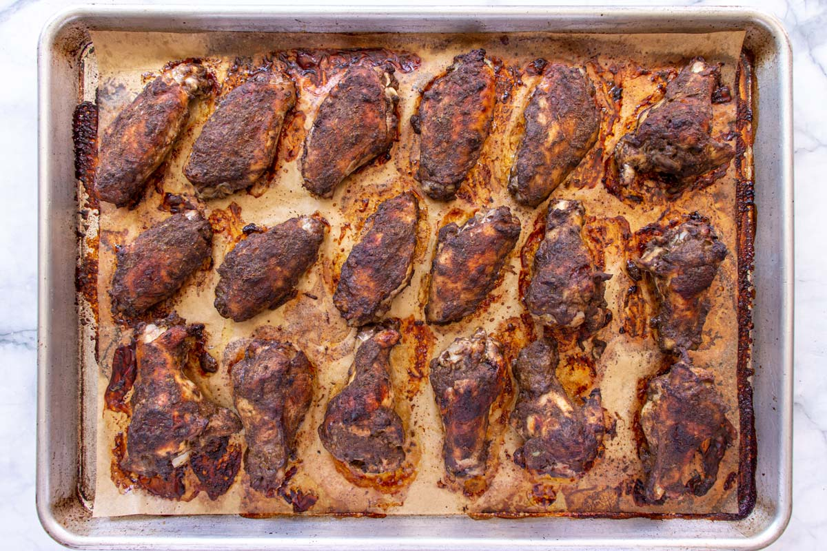 Baked jerk chicken wings on a parchment paper lined baking sheet.