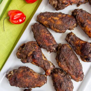 Closeup of Jamaican jerk chicken wings on a white rectangular plate next to 2 habanero peppers.