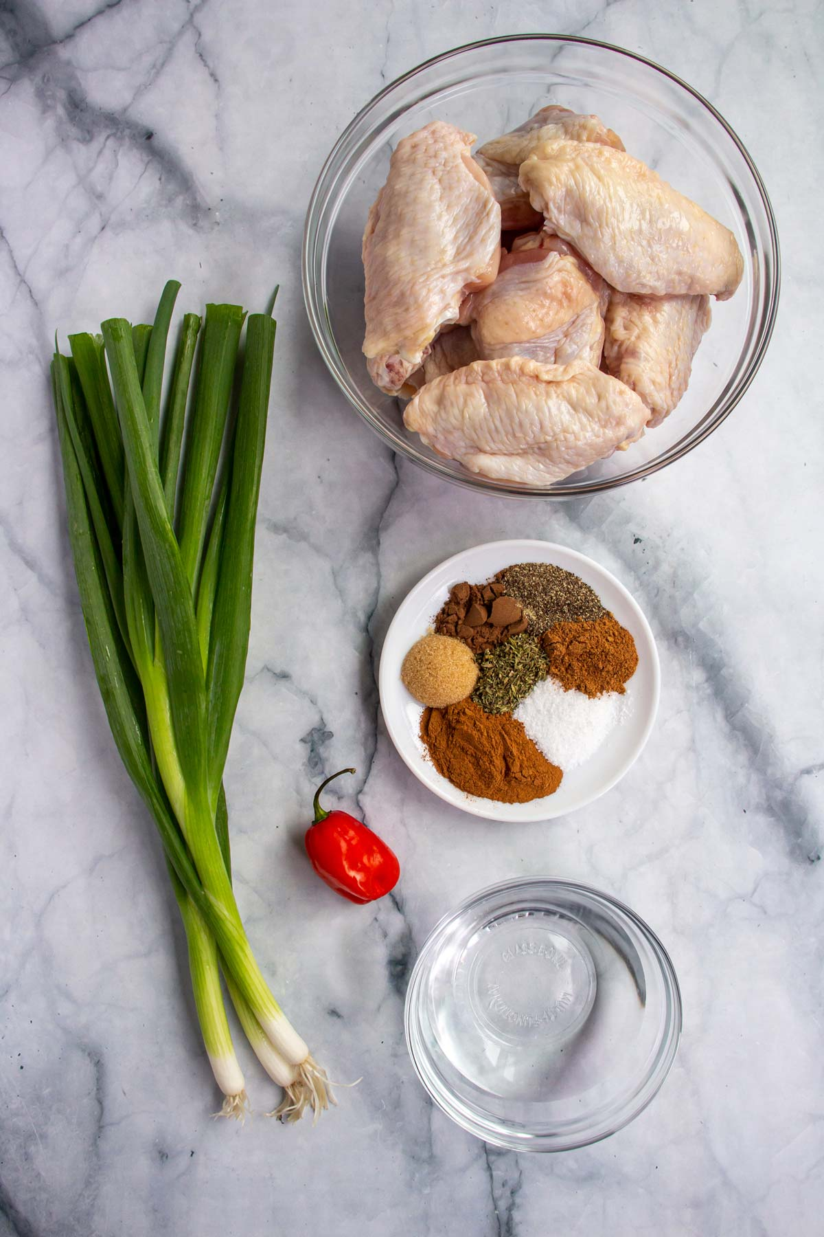 Ingredients for Jamaican jerk chicken wings on a white marble background.