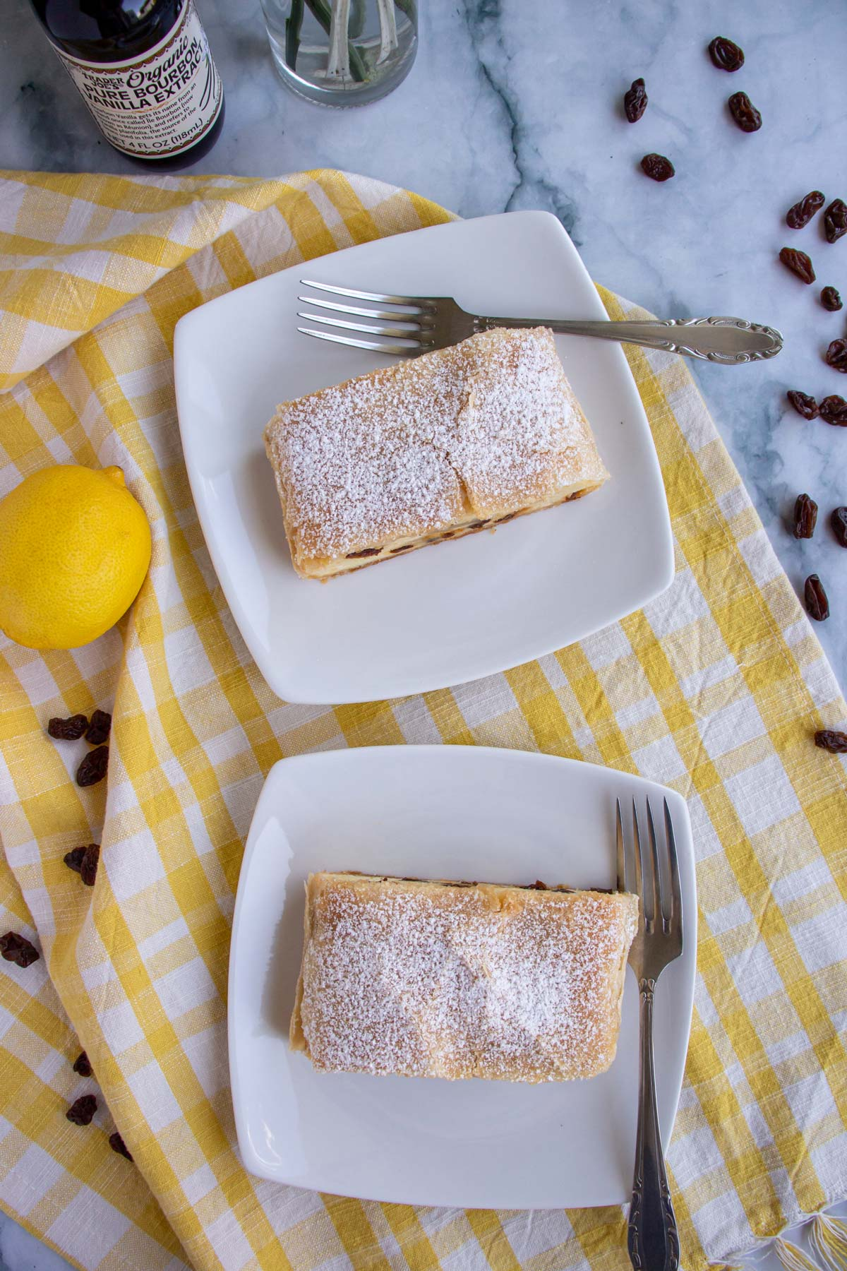 Two slices of powdered sugar topped strudel on white square plates on a yellow gingham towel.