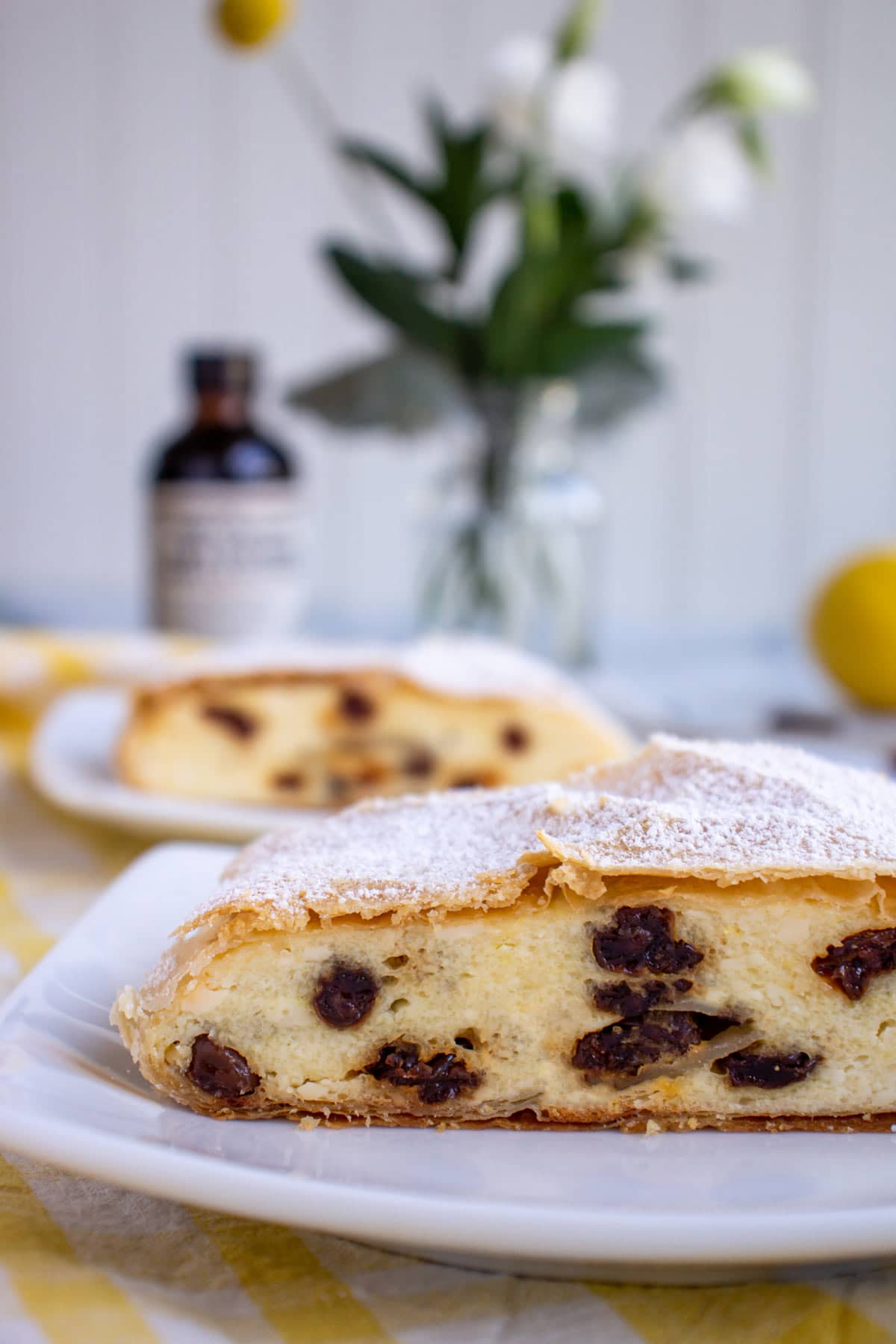 Closeup of a slice of cheese strudel with raisins with flowers in the background.
