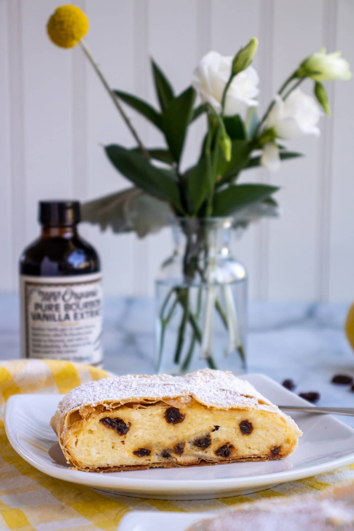 A slice of quark strudel with flowers and a bottle of vanilla extract behind it.