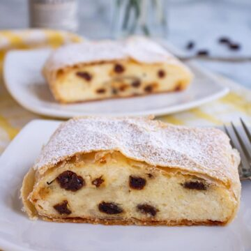 Two slices of cheese strudel with raisins topped with powdered sugar on small white plates.