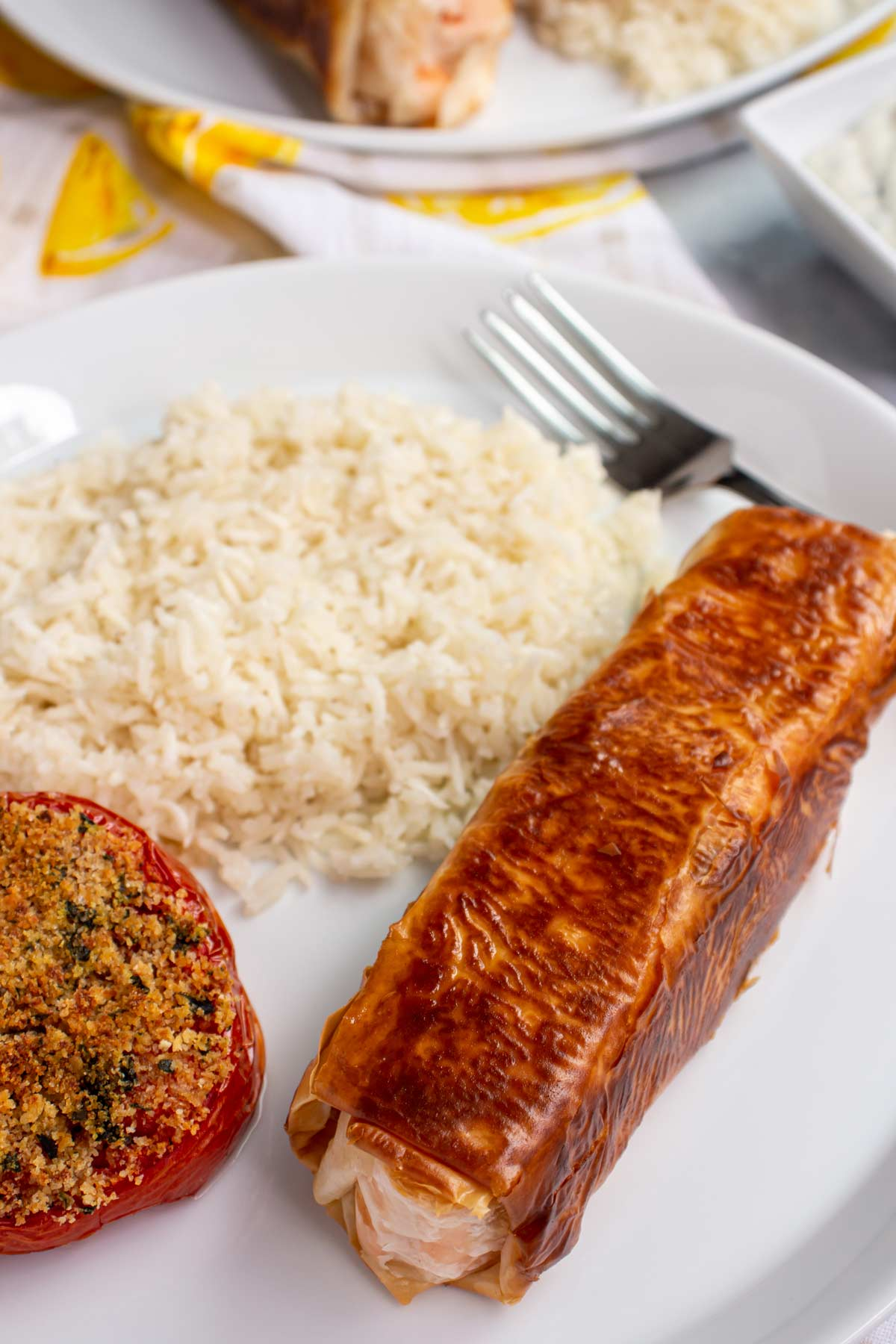 Closeup of phyllo wrapped salmon with white rice and baked tomato on a white plate.