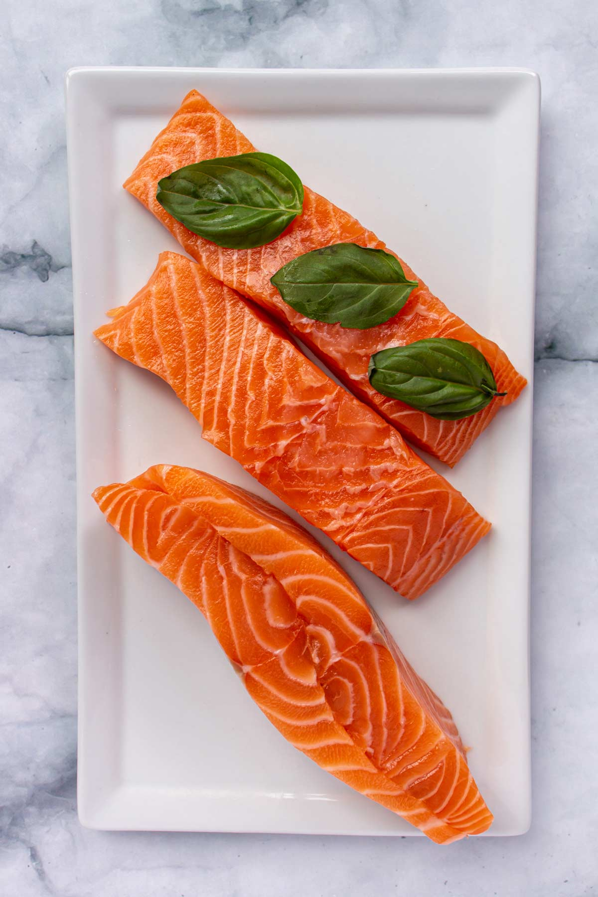 Assembling salmon fillets with basil sandwiched between them on a white plate.