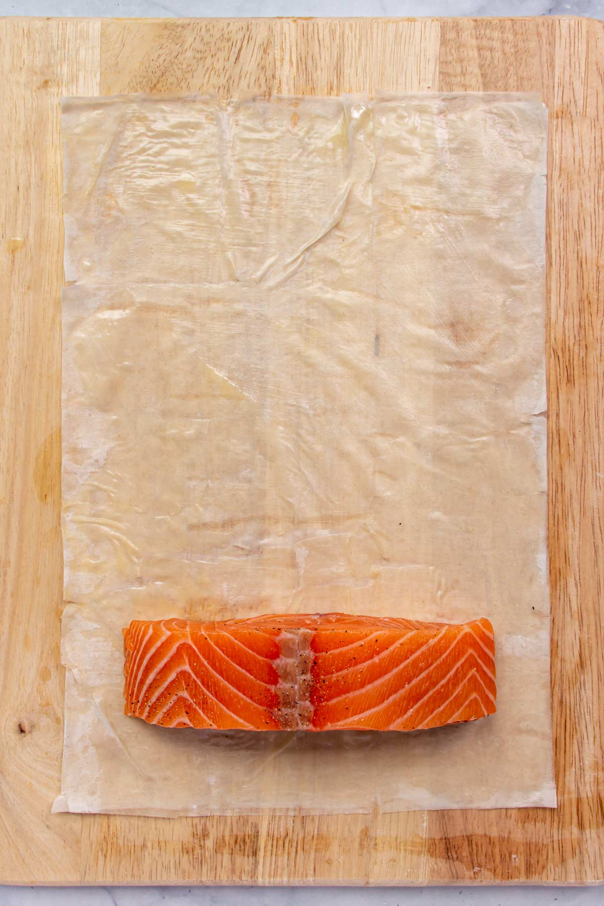 A salmon fillet on one end of a sheet of phyllo dough on a wooden board.