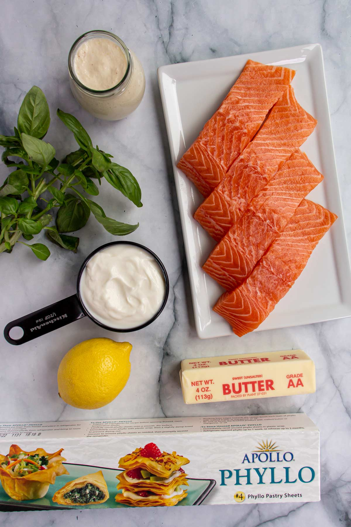 Ingredients for wrapped salmon in phyllo dough on a white marble background.