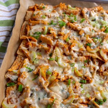 Buffalo chicken nachos with celery and scallions in rectangular pan with a striped towel next to it.